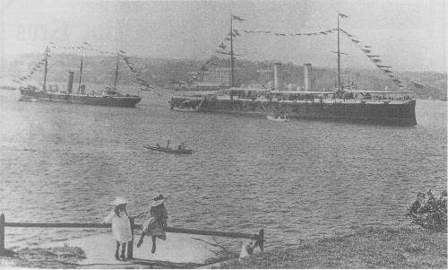 HMS Royal Arthur, Flagship of the Australia Station (Rear Admiral Beaumont RN) anchored in Farm Cove, Sydney, and dressed overall to celebrate the birth of Australian Federation on New Year's Day, 1901) Adjacent vessel is HMS Torch (sloop).