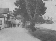 During the visit of the Duke of Gloucester to New Zealand a stop-over was made in the Bay of Islands. Seen here are some of the ship's company walking along the waterfront of the historic town of Russell. 26.1.35,