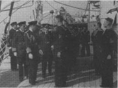 "On arrival at Portsmouth the Prince of Wales and the Duke of York came aboard to greet their younger brother. The Princes are seen here inspecting part of the ship's company at ""Divisions"". 28.3.35"