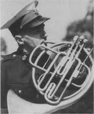 Photo of bandsman Cedric Ashton playing the French horn (WWII)