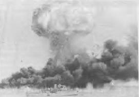 HMAS DELORAINE during the Japanese raid on Darwin, with oil tanks of fire in tbe background