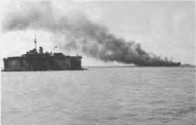 HMAS KATOOMBA high and dry in the floating dock with ship on fire in the baclaground