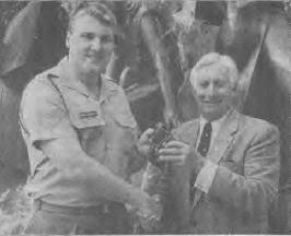 Sergeant Mark Holloway presents a pair of binoculars belonging to the late Commander J.F. Rayment to his son, Mike.