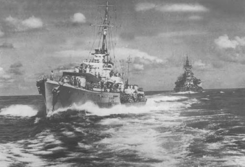 "The photograph shows the ""N"" class destroyer Nepal coming up astern of the battleship ""Queen Elizabeth"" to receive a package from Admiral Somerville. Astern is the battleship ""Valiant"". The officer standing in the destroyer's bow is Leut. Brian Murray (later Rear Admiral Sir Brian Murray). The writer of this article is on the flag deck."