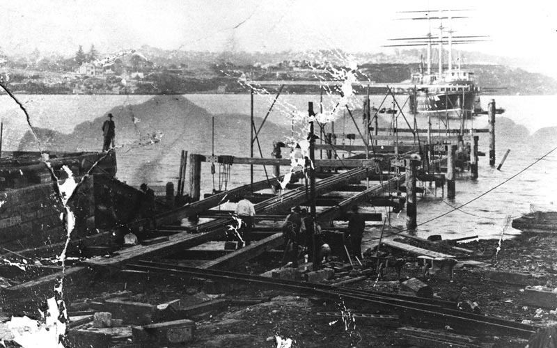 The 500 ton slipway under construction in 1909 with the school ship Sobraon in the background